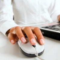 Woman's hands touching computer mouse and keys of black opened laptop